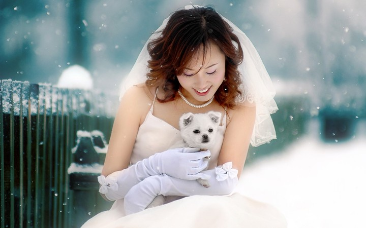 Asian Bride hold a Dog in snowflakes