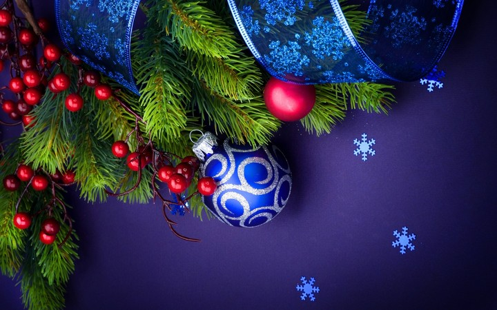 Christmas blue ball with ribbon over purple background