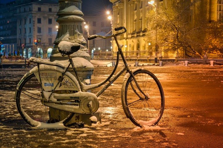 Bicycles covered with snow under the street lamp