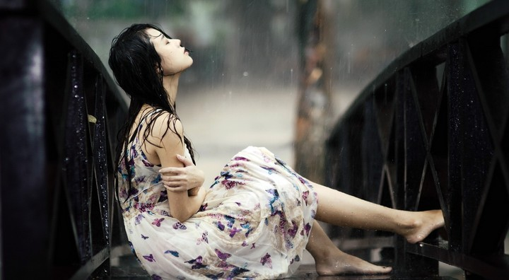 Young Girl Sitting On Steel Bridge In The Heavy Rain In The Park