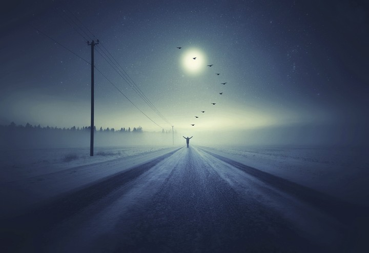 man walking on country road in the fog
