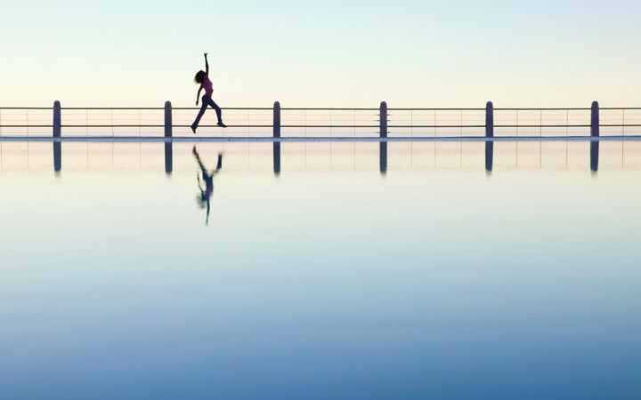 Silhouette Of Woman Jogging On Bridge At Sunrise