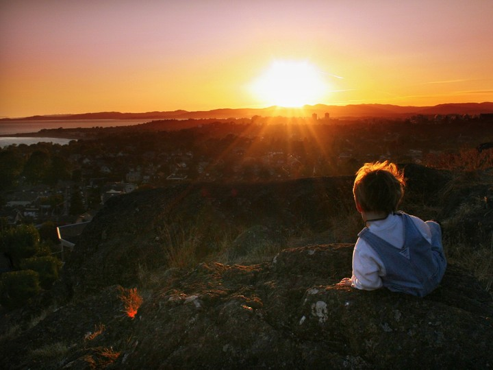Little Boy Watching The Sunrise At The Top Of The Mountain