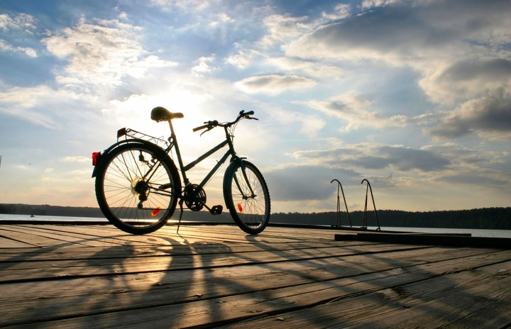 Old and vintage bicycle at the railing near the sea, sunset sky in background