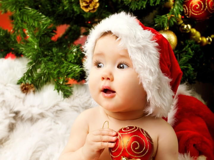 Cute baby in Santa hat and holding red ball decoration on hand hd