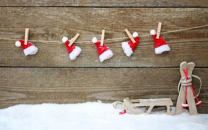 Red Christmas hats hanging over wooden background